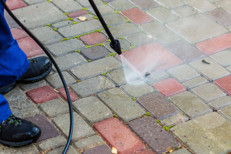 Cleaning pavement with a pressure water